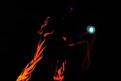 Die Körperspannung des Jongleurs ist durch das Schwarzlichtkostüm gut erkennbar